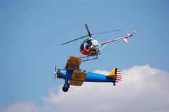 Barnstorming. A helicopter attempts to pick a wingwalker off of a Stearman Biplane stock image
