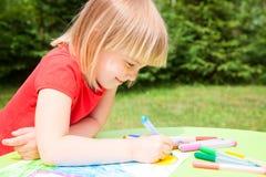 Barnteckning i en sommarträdgård Fotografering för Bildbyråer