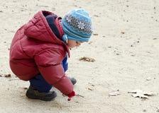 Barnteckning in i sand Arkivfoton