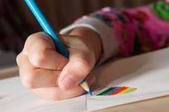 Barnteckning med blåttblyertspennan Arkivfoto