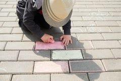 Barnteckning med krita på asfalt pojke som bara spelar i gatan rymma ett stycke av krita i hans fingrar royaltyfri fotografi