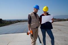 Barnteknikerflicka och kompetent arbetare på ett tak arkivfoto
