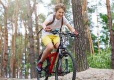 Barntonåring i den vita t-skjortan och gula kortslutningar på cykelritt i skog på våren eller sommar Lyckligt le cykla för pojke  fotografering för bildbyråer