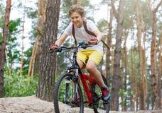 Barntonåring i den vita t-skjortan och gula kortslutningar på cykelritt i skog på våren eller sommar Lyckligt le cykla för pojke royaltyfri bild