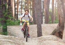 Barntonåring i den vita t-skjortan och gula kortslutningar på cykelritt i skog på våren eller sommar Lyckligt le cykla för pojke  arkivfoton