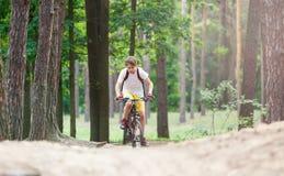 Barntonåring i den vita t-skjortan och gula kortslutningar på cykelritt i skog på våren eller sommar Lyckligt le cykla för pojke  arkivbild