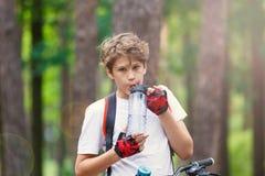 Barntonåring i den vita t-skjortan och gula kortslutningar på cykelritt i skog på våren eller sommar Lyckligt le cykla för pojke royaltyfria foton