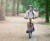 Barntonåring på cykelritt i skog på våren eller sommar Lycklig le pojke som utomhus cyklar i blå hjälm aktiv livsstil arkivfoto