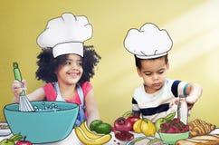 Barnungar som lagar mat kökgyckelbegrepp royaltyfri foto