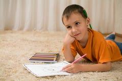Barnunge med blyertspennor på mattan. Arkivbilder
