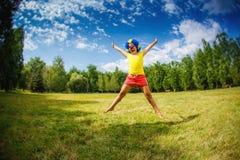 Barnungeflickan med lyckligt för peruk för particlownblått roligt öppnar armar uttryck, och girlander hoppar Royaltyfri Foto