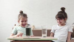Barnuppförandekemikalien experimenterar hemma två små flickor observerar en kemisk reaktion Vetenskap för barn stock video