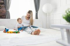 Barnutbildning Lycklig moder med hennes litet barnsammanträde på sängen och läsningen en bok arkivfoton