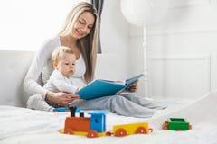 Barnutbildning Lycklig moder med hennes litet barnsammanträde på sängen och läsningen en bok royaltyfria foton