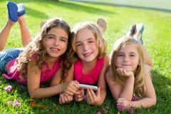 Barnvänflickor som leker internet med smartphone Fotografering för Bildbyråer