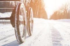 Barnvagn med uppblåsbara hjul på vintersnövägen under den ljusa solen på den ljusa dagen Royaltyfria Foton