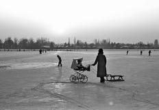 Barnvagn och pulka på den djupfrysta gamla Donauen Arkivbild