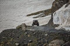 Barnvagnberg som kör på vägen med snöytterlighet arkivbild
