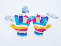Barnvinterhandskar i snö royaltyfria foton