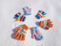 Barnvinterhandskar i snö fotografering för bildbyråer