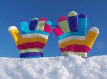 Barnvinterhandskar i snö arkivbilder
