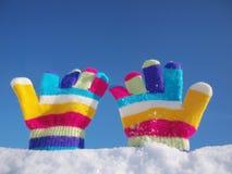 Barnvinterhandskar i snö arkivfoto
