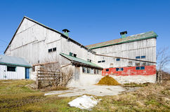 Barnyard and Barn. A barn sits in the corner of a barnyard on a clear blue sky day Royalty Free Stock Photo