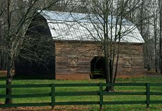 Barnyard In Early Spring. Barn and fence in ealy spring with new green grass and still bare trees Stock Photo