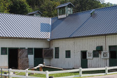 Barnyard Square. A barn and white rail fence create a barnyard square enclosure with goats Stock Photography