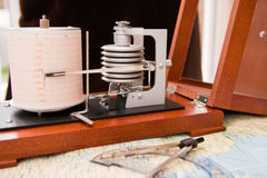 Barograph. In a wooden box with the lid open standing on a map Royalty Free Stock Photo