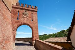 Barolo medieval castle entrance arch in red bricks in Italy. BAROLO, ITALY - AUGUST 6: Barolo medieval castle entrance arch in red bricks and emblem with empty Royalty Free Stock Image