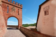 Barolo medieval castle entrance arch in red bricks, Italy. BAROLO, ITALY - AUGUST 6: Barolo medieval castle entrance arch in red bricks and emblem with empty Stock Photo
