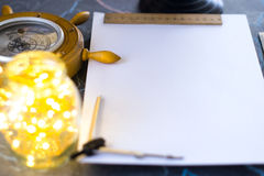 Barometer on a background of a white sheet of paper with lights in a glass jar. Stock Photo