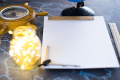 Barometer on a background of a white sheet of paper with lights in a glass jar. royalty free stock photo