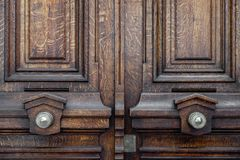 Vintage ornate metal doorknobs of aged wooden double door in Paris France. Symmetric handles and dark wood texture of old door. Baroque architecture of Paris royalty free stock photography
