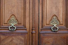 Two antique ornate brass knockers of aged wooden door in Paris France. Metal patterned handles and wood texture of old double door royalty free stock photo