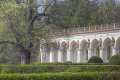 Baroque colonnade with statues and hedges Stock Image