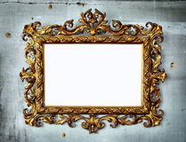 Baroque frame. Beautiful golden baroque frame hanged in an old wall with holes and cracks Stock Image