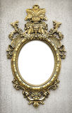 Baroque Frame. Beautiful and complex golden baroque frame hanged on a textured wall Royalty Free Stock Photos