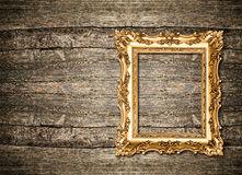 Baroque golden frame over wooden background. Grungy texture Royalty Free Stock Image
