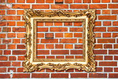 Baroque golden frame on red brick wall Stock Photography
