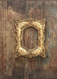 Baroque golden frame on wooden background. Grunge texture Stock Image