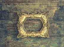 Baroque golden frame on wooden background. Grunge texture Stock Photo