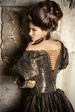 Baroque lady. Art Fashion. Beautiful young woman in elegant historical dress and with barocco updo hairstyle posing in the ruins of the castle. Renaissance Stock Photography