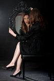 Baroque Mirror girl. Girl staring in a mirror with a black baroque frame in black dress and with red lips royalty free stock photos