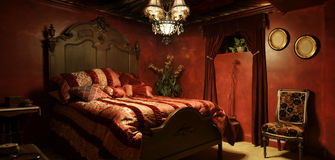 Baroque red bedroom. Vintage antique feel, predominant red colors, red walls, chandelier, chair, curtains, bed Stock Images