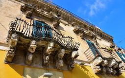 Baroque sculptures in Modica. Balcony with typical baroque sculptures in Modica, Sicily, Italy stock images