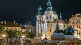 Baroque St. Nicholas' Cathedral on the Oldtown Square in Prague with monument Jan Hus illuminated at night timelapse. Tourists walk around stock video footage