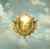 Baroque sun. Artistic imagine of a baroque sculpture of representing the sun in the cloudy sky in the background stock illustration