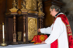 Baroque tabernacle. Baroque antique tabernacle with priest returning the chalice after holy mass in a medieval church Royalty Free Stock Photos